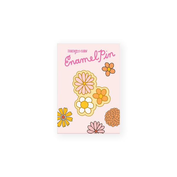enamel pin of three daisy flowers in pink, white and orange