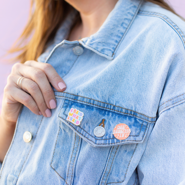 "girl in denim jacket with pins saying ""I said what I said"" and ""deep breaths in"""