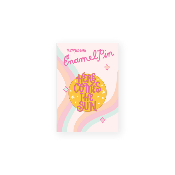 round enamel pin with yellow ground and pink letters saying here comes the sun
