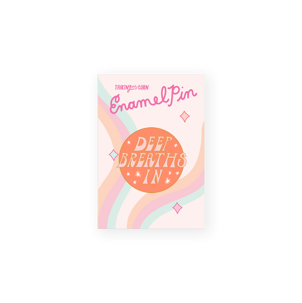 round enamel pin with orange background and pink words saying deep breaths in