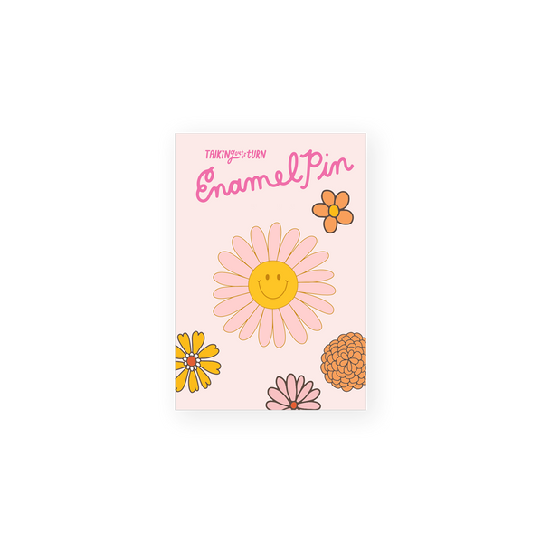 pink daisy enamel pin with yellow smiley face in center