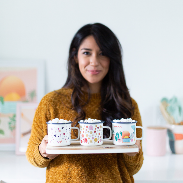 a girl holding three campfire mugs. one with flowers, one with a sunset and plants, and one terrazzo