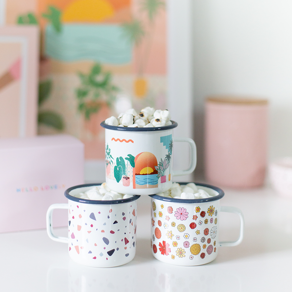 a stack of three campfire mugs one with flowers, one with a sunset and plants, and one terrazzo