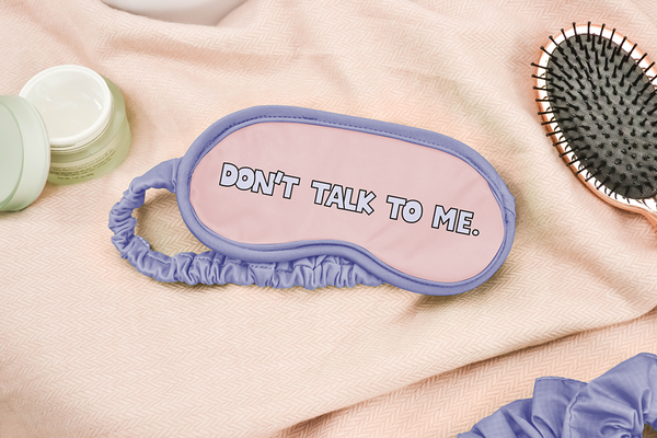 A sleep mask with periwinkle outline and strap that says don't talk to me laying next to a gold brush and moisturizer