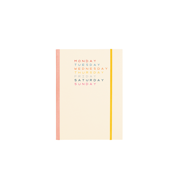 Cream planner with peach binding and yellow elastic closure featuring each day of the week printed in a different color.
