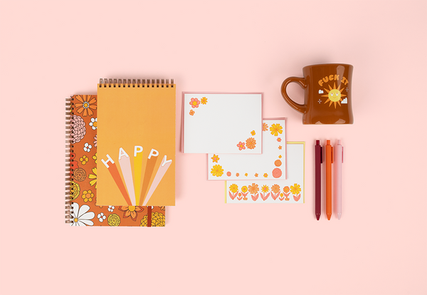 cute set of notebooks one with flowers, one saying happy with a set of letterpress notecards with flowers, set of pens and a brown diner mug with the saying fuck it with sunshine