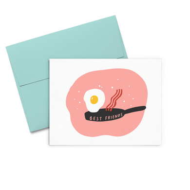 Letterpress greeting card with a cute fried egg and a piece of bacon jumping out of a skillet that says Best Friends all on a peachy circle background