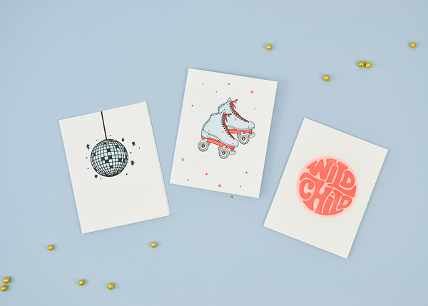 "A collection of white greeting cards. From left to right: A light blue and black disco ball. A light blue and coral pair of skates. A coral and red circular graphic with ""Wild Child""."