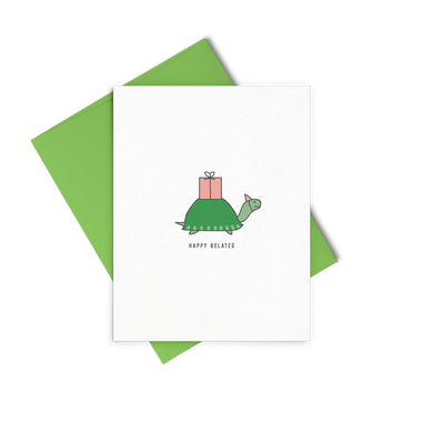 Happy Belated is a cute birthday card of a little turtle with a pink gift on his back and wearing a pink party hat.