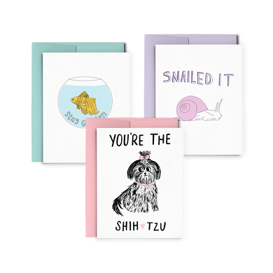 Three letterpress greeting cards stacked, one has a goldfish in a fishbowl and says Stay Golden, one has a purple snail and says Snailed It, and one has a doodle of a dog and says You're The Shih Tzu.