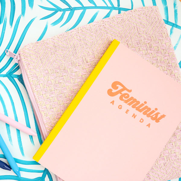 A small peach notebook that says Feminist in orange across the cover sitting on  a pink straw dollface pouch