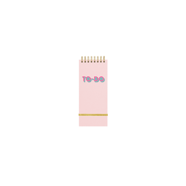 Small pink taskpad with a metallic gold elastic closure and To Do written on the cover