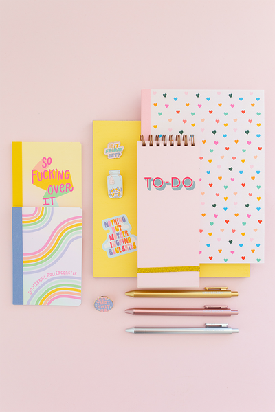 stack of different sized notebooks with different patterns, metallic pens and enamel pins