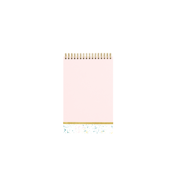 Pink taskpad with a metallic gold elastic closure and small white section of paint splatter at the bottom