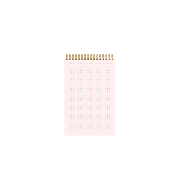 Inside page of a gold wire-bound pink taskpad showing a tiny dot grid pattern.