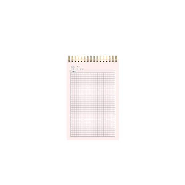 Inside pink page of a gold wire-bound taskpad showing a grid paper design.