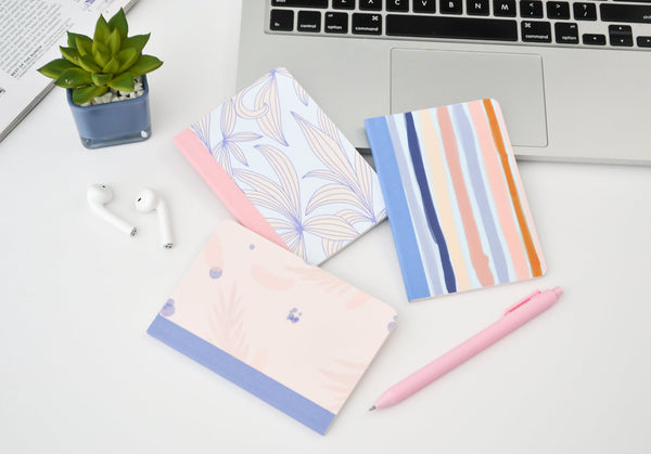 three mininotebooks next to a laptop, airpods, a plant, and a pink jotter pen. One notebook has periwinkle leaves, one has stripes, and one is a watercolor