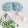 A weighted eye mask in a green terrazo print is sitting next to a light pink vegan leather zippered pouch. The pouch has a green leaf print all over it and has two stone face rollers tucked into it.