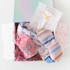 A gift set containing a clear glass mug with Killing It written in blue, a neck wrap with small flowers, a striped eye mask, and a face roller all in pink crinkle paper and packaged in a colorful box.