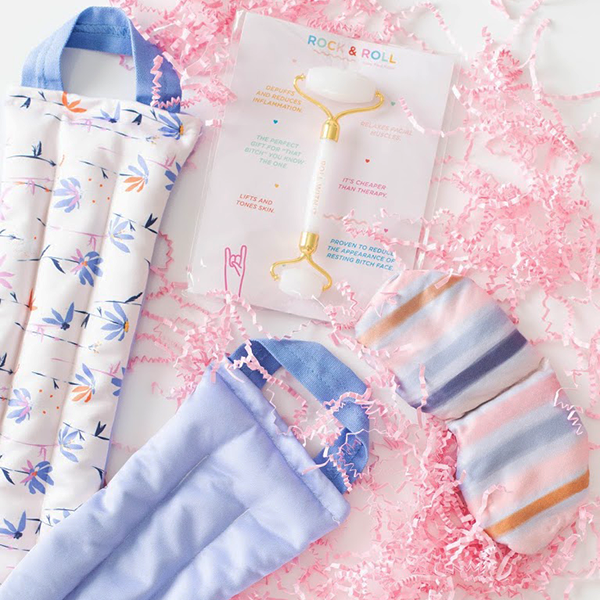 Contents of a gift set laid out to show the floral patterned neck wrap, a weighted eye mask with blue stripes printed on it, and a white quarts face roller amidst pink paper shreds.