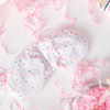 A light pink weighted eye mask with multi colored hearts printed all over. There is a clear glass mug in the bottom right corner and light pink crinkle paper scattered all over.