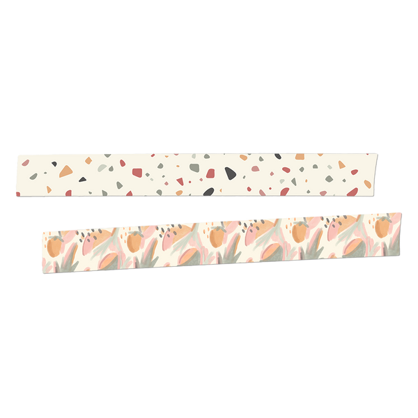 Two rolls of washi tape rolled out.  The first is white with a grey, blue, red, yellow and brown terrazzo pattern. The second roll is a watercolored botanical and fruit pattern in light green, corals, orange and pink.
