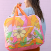 girl holding large stowaway tote bag over her shoulder in colorful pink floral and swirl patter