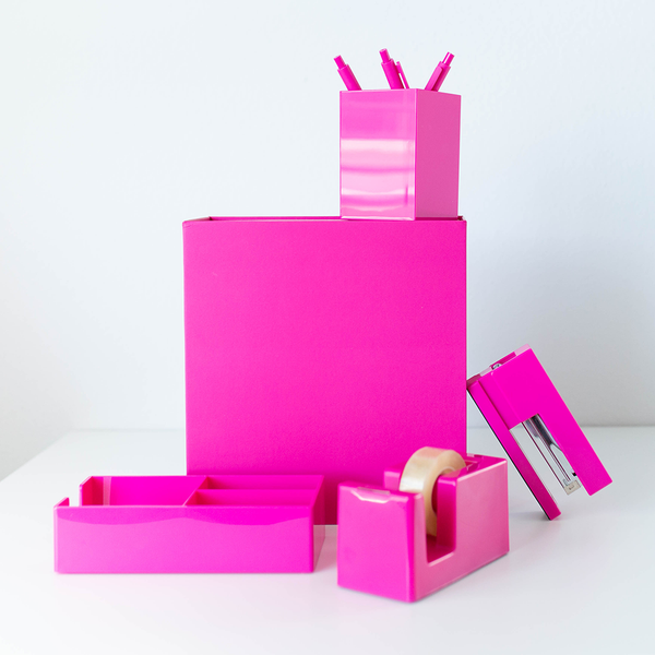 A pink desk set stacked around a pink gift box.