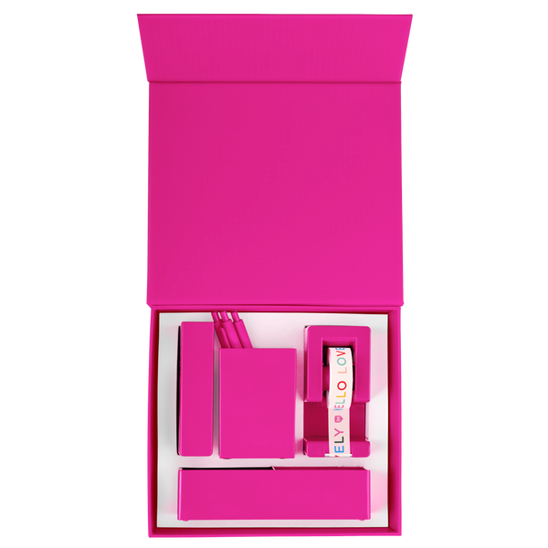 Overhead view of an opened pink desk set with a pink stapler, tray, tape dispenser, and pen cup with pens all nestled in a foam insert.