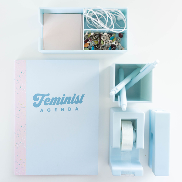 "Image of a powder blue desk set surrounding a light blue notebook with the text ""Feminist Agenda"""