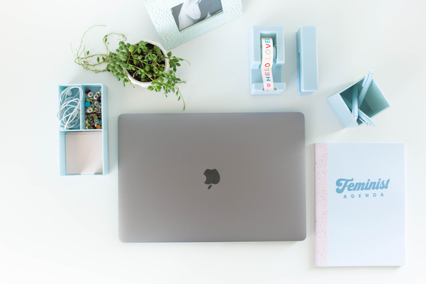 "Image of a powder blue desk set surrounding a laptop. There is a green plant and a light blue notebook with the text ""Feminist Agenda"""