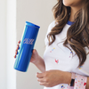 A woman holding a royal blue stainless steel tumbler that reads
