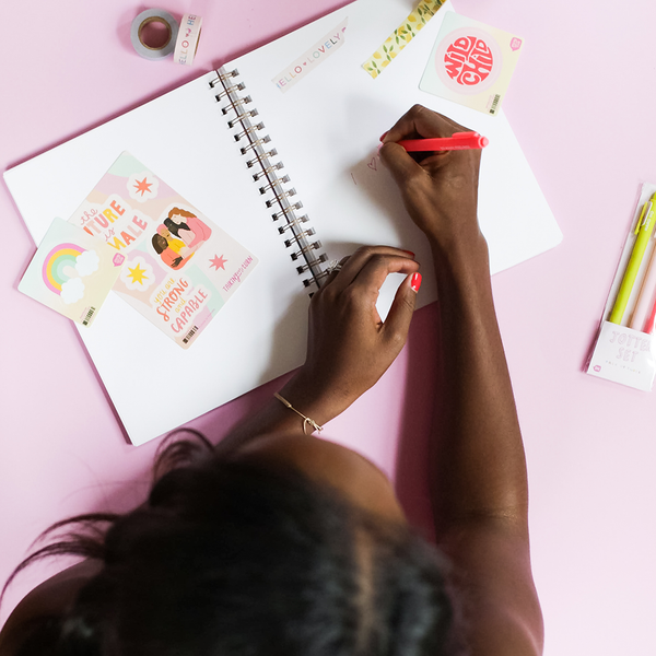a girl writing in a notebook with a cute pink, yellow, teal, and blue rainbow sticker on top
