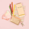 A metallic gold penny pouch with a key ring surrounded by a pastel face mask, jotter pens, a notebook and a to-do taskpad.