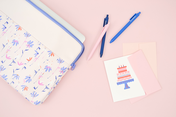 A white greeting card with a layered birthday cake on a cake stand and 3 candles on top. There is a magic sprigs laptop sleeve and three jotter pens on a pink background.