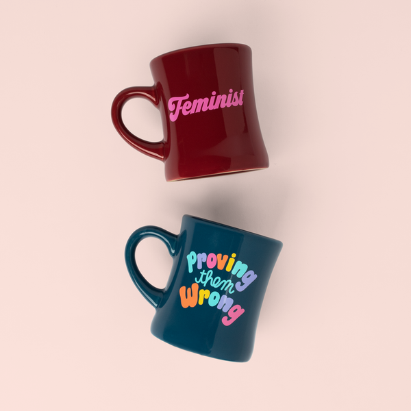 two old school diner mugs- one sangria with feminist in pink and a navy one with colorful letters saying proving them wrong?id=28703084740789