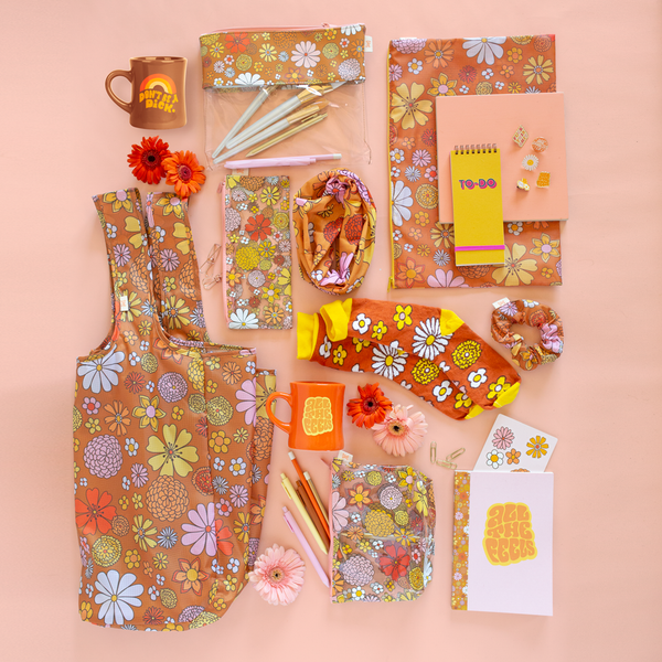 Collection of floral printed pouches, coffee mugs, notebooks, pins and socks laid out