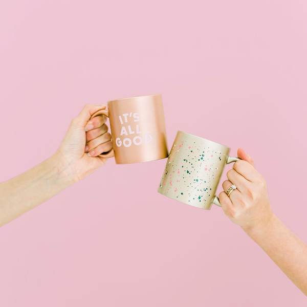 Two hands holding two metallic mugs one that reads It's All Good and one with multi-color speckles.