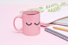 Pink funny coffee mug with thick black eyelashes printed on the front next to buds laptop sleeve
