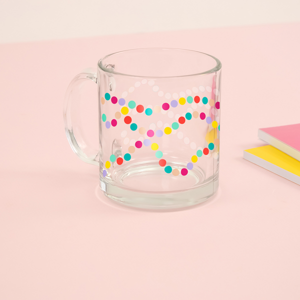 Multi colored polka dot clear glass mug sitting on a pink table