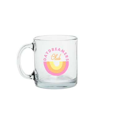 A glass mug with the words day dreamers club printed in an oval in pink and yellow colors in the middle of the glass.