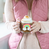 a girl holding a cute glass mug with a rainbow that says fuck mornings