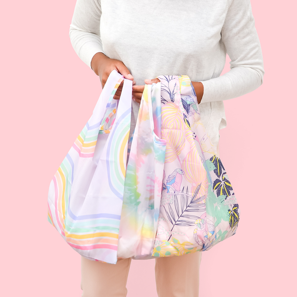 girl holding four different pastel patterned totes in hands