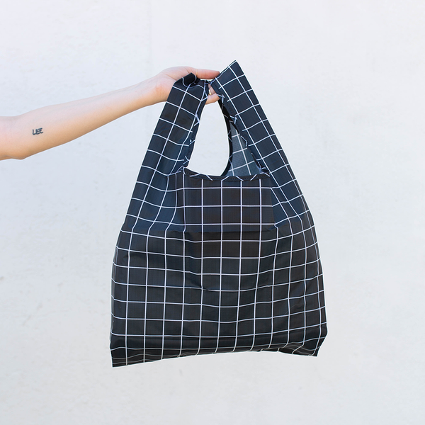 Image of a woman's hand holding a black and white grid pattern tote bag
