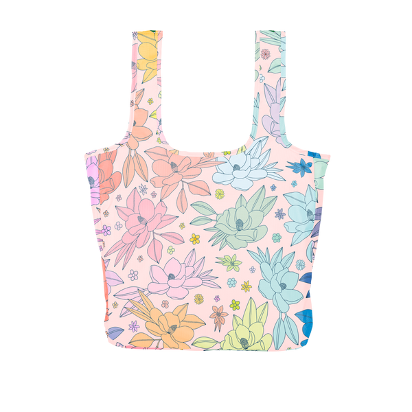 A large pink reusable tote with multi-colored magnolia flowers.