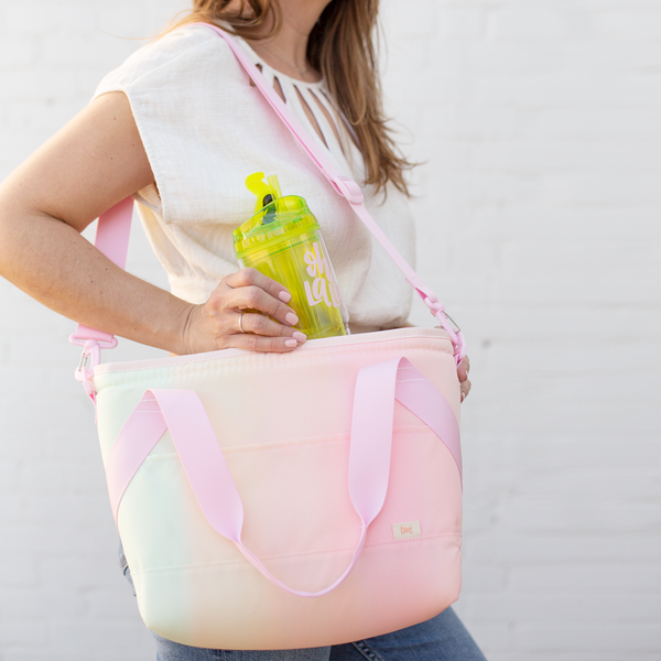 girl holding cute pastel ombre soft cooler bag over shoulder pulling a drink out of it