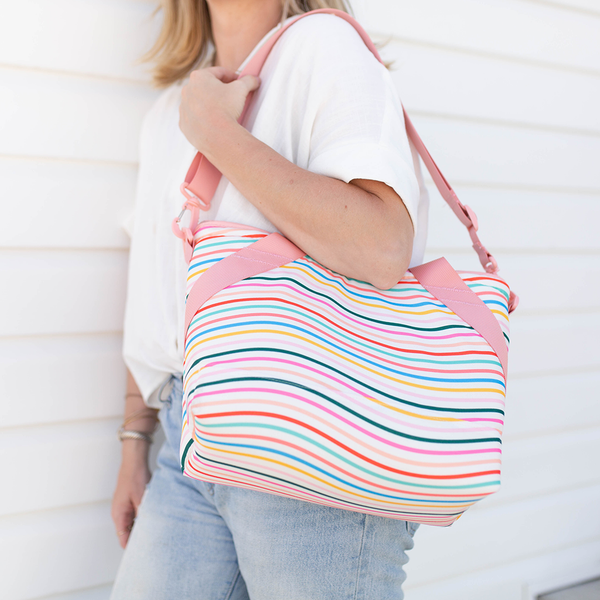 a girl holding a small soft-sided cooler with different color stripes
