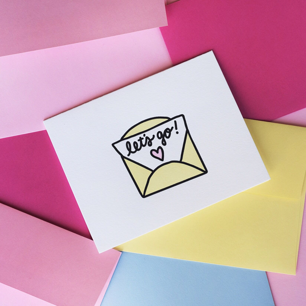"White greeting card with a yellow, black and pink graphic. The graphic is a yellow envelope with a paper sticking out with script text ""let's go!"" and a pink heart."