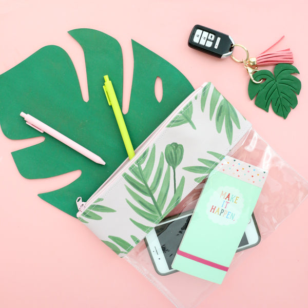 Cute pencil pouch lying on a monstera leaf with pens, car keys, and a Make It Happen taskpad.