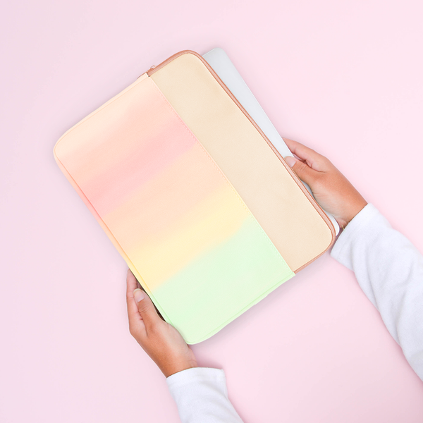 Hands holding a rainbow gradient laptop sleeve